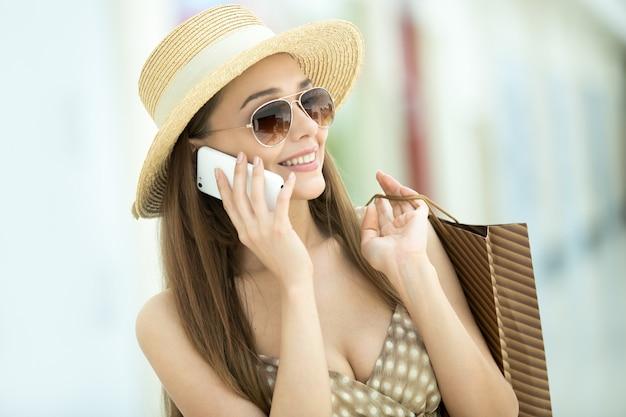 Rapariga com chapéu de palha que fala no telemóvel