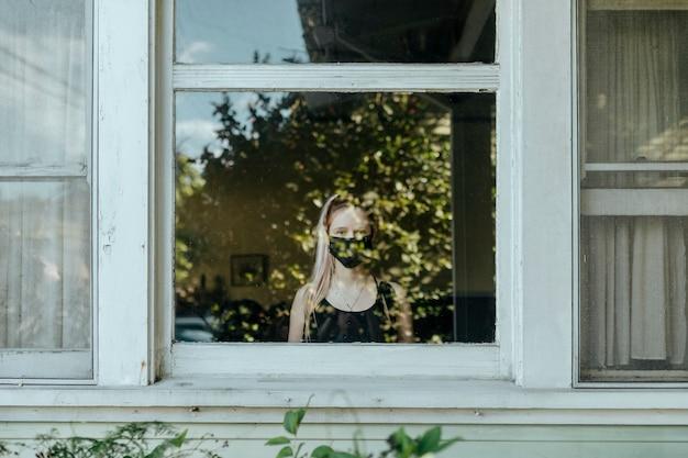 Rapariga com máscara a olhar pela janela durante um bloqueio