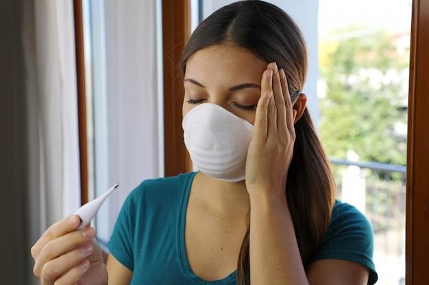 Rapariga com máscara no rosto verifica febre um dos sintomas da doença do coronavírus 2019.