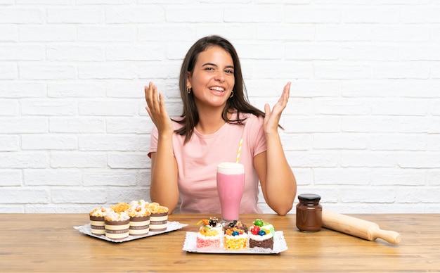 Rapariga com muitos mini bolos diferentes infelizes e frustrados com algo