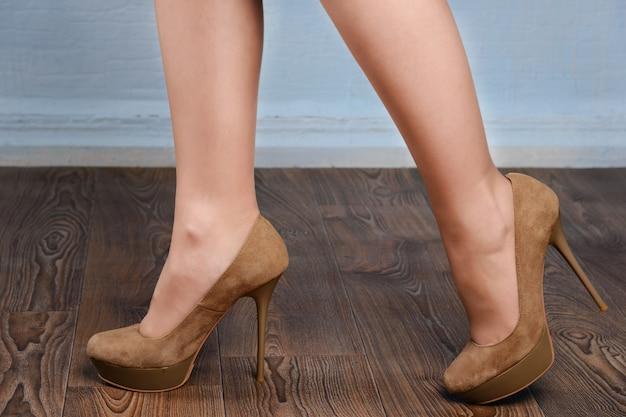 Rapariga com sapatos de salto alto de camurça bege no chão de madeira