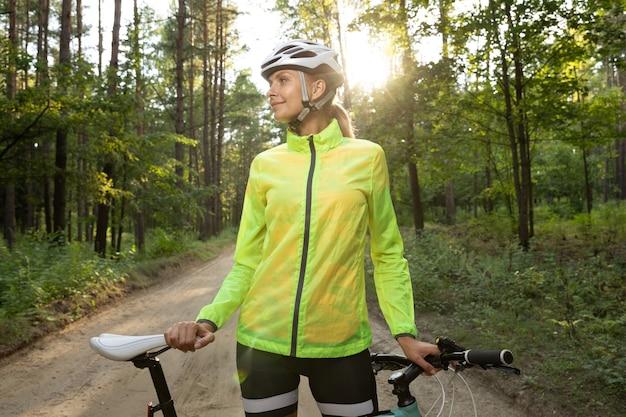 Rapariga com um casaco verde brilhante, calção e capacete a descansar depois de um passeio de bicicleta na floresta