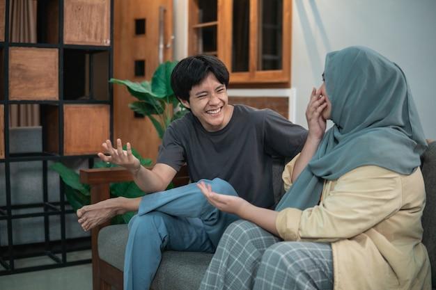 Rapariga com um hijab e um homem riem alegremente na sala de estar, sentados numa cadeira de madeira