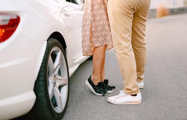 Rapariga com um vestido colorido na ponta dos pés perto de um homem com calças amarelas