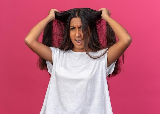 Rapariga com uma t-shirt branca a parecer frustrada a puxar o cabelo à solta