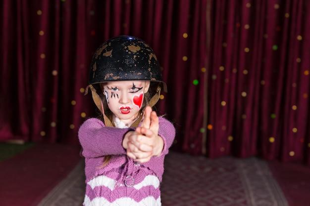 Rapariga de aparência difícil usando capacete de combate com as mãos unidas para formar uma arma apontada para a câmera e em pé no palco com uma cortina vermelha no fundo
