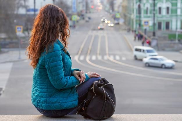 Rapariga de cabelo ruivo olha para a rua à noite na cidade