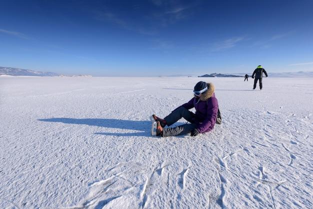 Rapariga de patins para patinar no gelo sentada no gelo e amarra, rússia, lago baikal