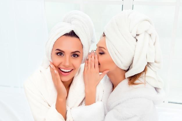 Rapariga de roupão e toalha na cabeça contando um segredo para a irmã