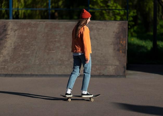 Rapariga de tiro completo de pé no skate