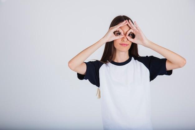 Rapariga e binóculos com os dedos