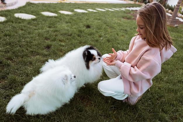 Rapariga e cachorrinhos brancos fofos brincando de vista alta
