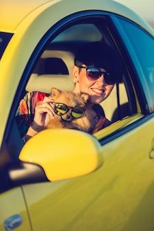 Rapariga e cão no carro na viagem de verão