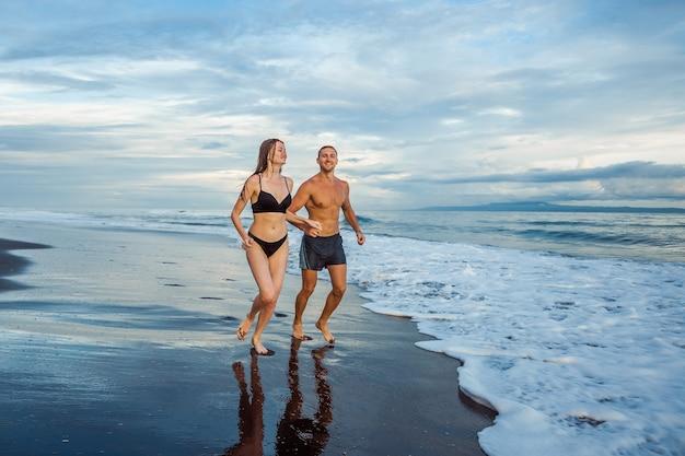 Rapariga e homem na praia a correr