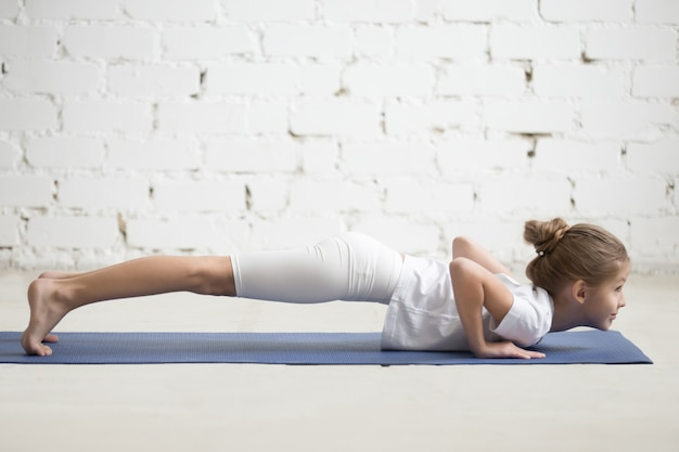 Rapariga em chaturanga dandasana pose, estúdio branco, closeup