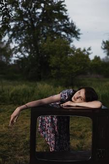 Rapariga em depressão deita-se numa caixa de moldura vintage vazia da televisão, saúde mental