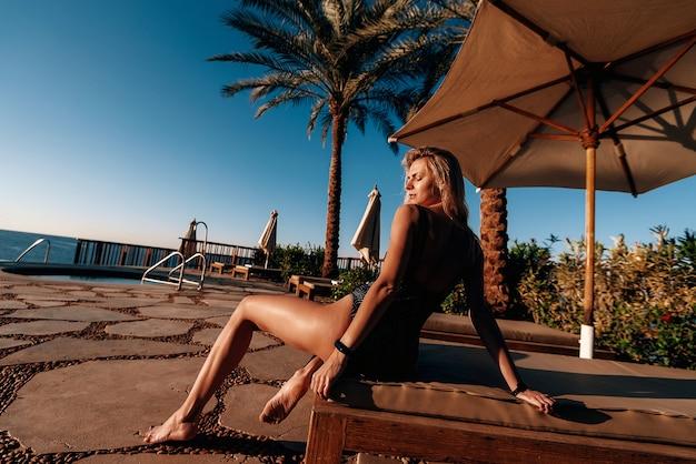 Rapariga em fato de banho na praia perto da piscina, ao sol quente, a relaxar nas férias