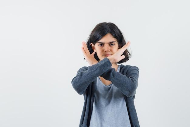 Rapariga em pé de braços cruzados, mostrando gesto de restrição em uma camiseta cinza claro e um capuz cinza escuro com zíper frontal e parecendo séria.