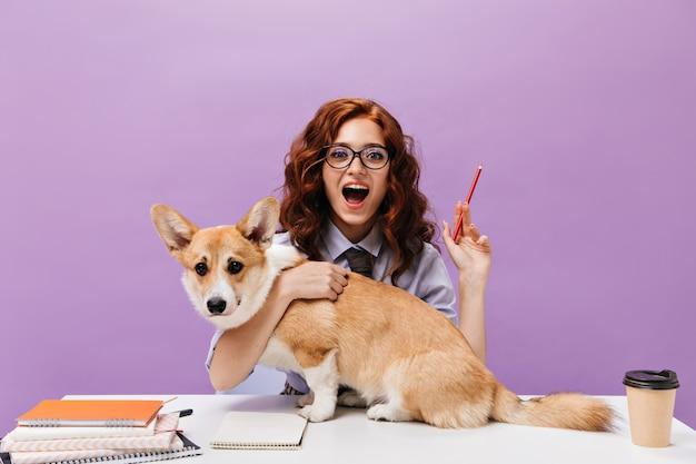 Rapariga encaracolada com camisa e óculos a abraçar cão e a segurar um lápis