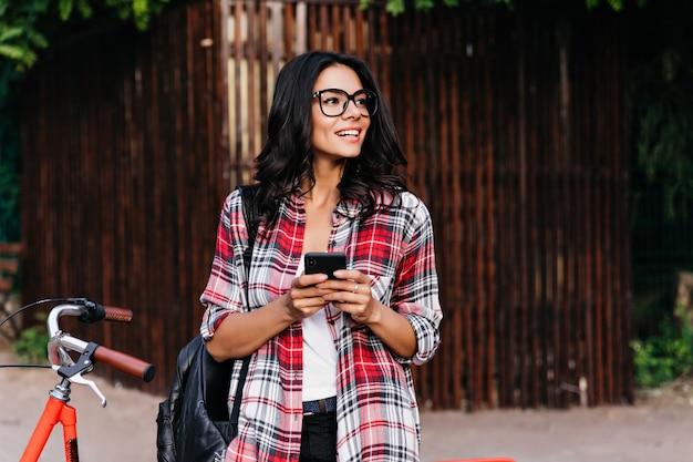 Rapariga encaracolada em êxtase na camisa quadriculada vermelha em pé na frente da bicicleta. retrato ao ar livre da senhora latina bem humorada com telefone, olhando ao redor da rua.