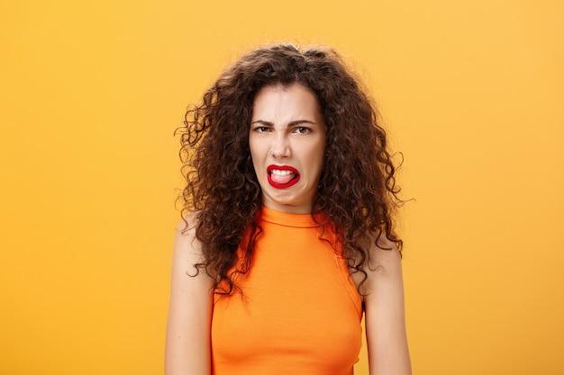 Rapariga enojada com comida de linha, mostrando a língua e franzindo a testa, mostrando aversão e nojo tal ...