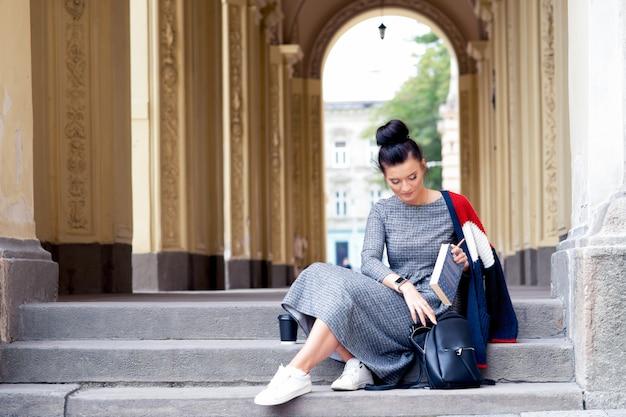 Rapariga estudante está colocando os livros na mochila preta nas escadas da universidade.