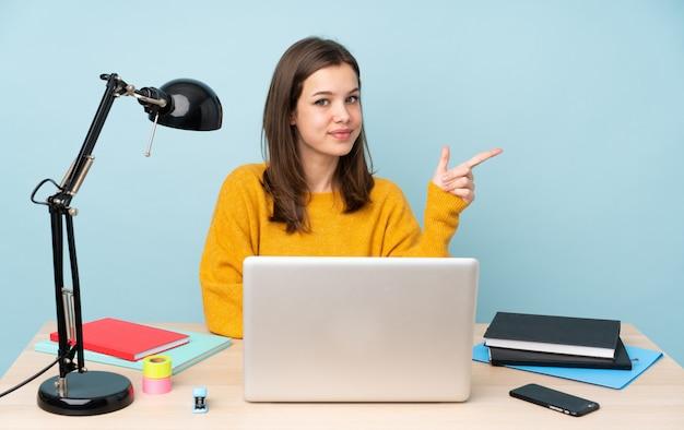 Rapariga estudante estudando em sua casa isolada na parede azul, apontando o dedo para o lado