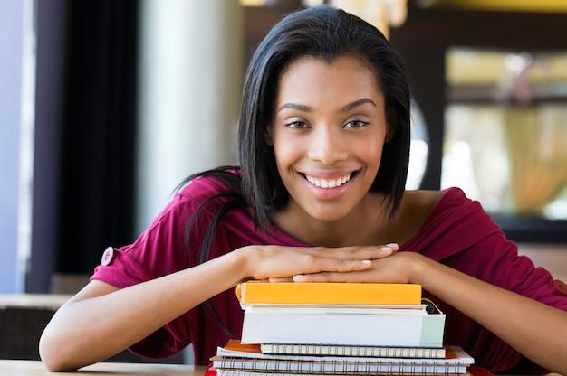 Rapariga estudante inclina-se na pilha de livros