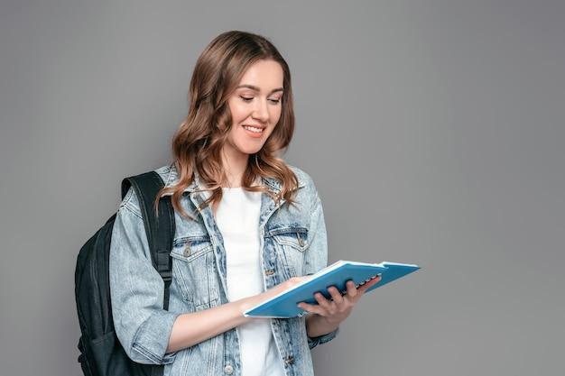 Rapariga estudante segurando um caderno com dever de casa nas mãos dela lendo e sorrindo isolado sobre o fundo da parede cinza