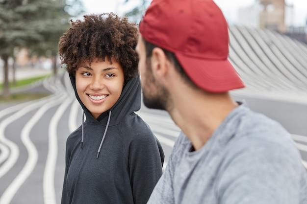 Rapariga fofa étnica sorridente de casaco com carapuço tem uma conversa agradável e amigável com um rapaz, passear