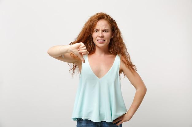 Rapariga jovem ruiva desnorteada em roupas leves casuais posando isolado no retrato de estúdio de fundo de parede branca. conceito de estilo de vida de emoções sinceras de pessoas. simule o espaço da cópia. mostrando o polegar para baixo.