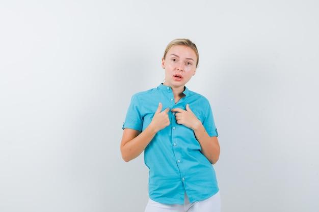 Rapariga loira a apontar para si própria com os dedos indicadores numa blusa azul isolada