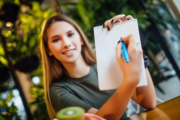 Rapariga loira a escrever um plano de dieta no bloco de notas