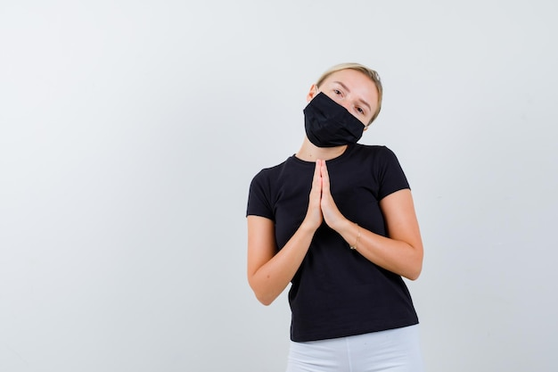 Rapariga loira a juntar as mãos em posição de oração numa t-shirt preta isolada