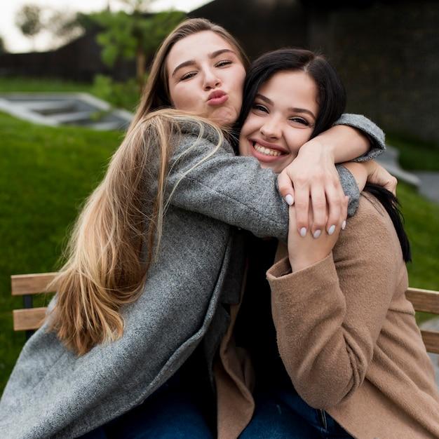Rapariga loira abraçando a amiga