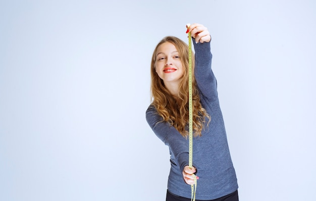 Rapariga loira abrindo a fita métrica e mostrando o resultado.