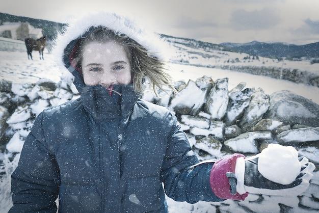 Rapariga loira brincando com bola de neve no inverno