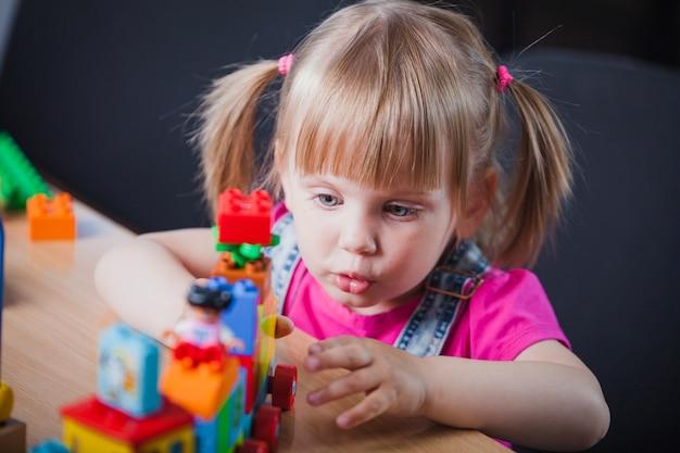 Rapariga loira brincando com trem de brinquedo