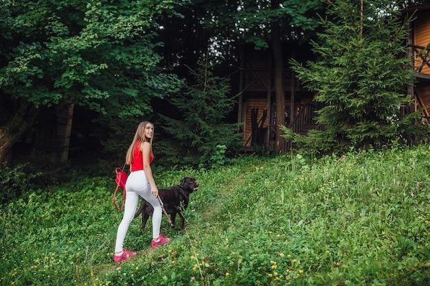 Rapariga loira caminhando no parque com seu labrador marrom