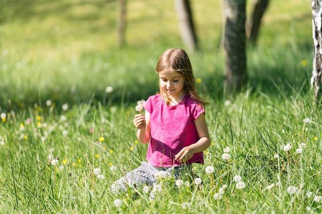 Rapariga loira colhendo flores dente de leão soprando sentada na grama verde no campo