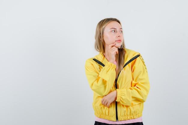 Rapariga loira colocando o dedo indicador perto da boca, segurando a mão no cotovelo, pensando em algo em uma camiseta rosa