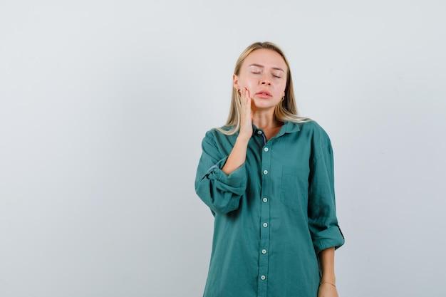 Rapariga loira com blusa verde com dor de dente e parecendo exausta