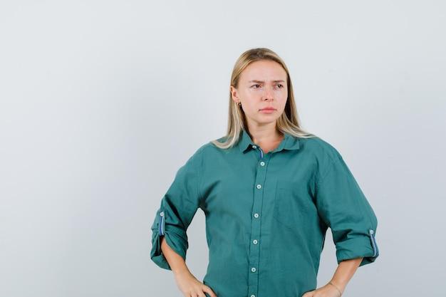 Rapariga loira com blusa verde de mãos dadas na cintura e parecendo pensativa