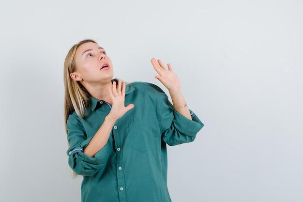 Rapariga loira com blusa verde levantando as mãos para parar e parecendo assustada