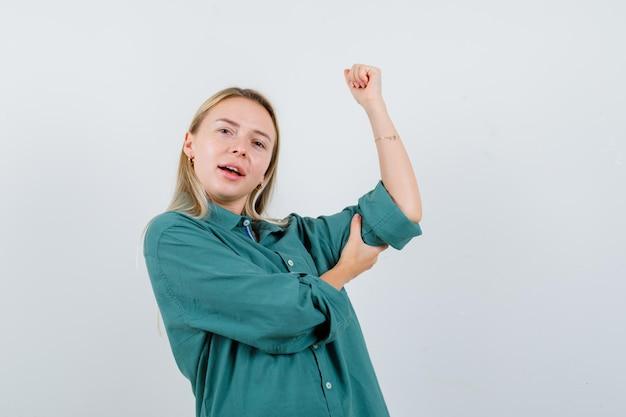 Rapariga loira com blusa verde mostrando gesto de poder e parecendo radiante