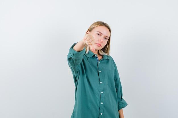Rapariga loira com blusa verde mostrando o polegar para baixo e parecendo descontente