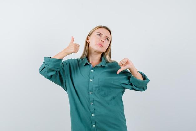 Rapariga loira com blusa verde mostrando o polegar para cima e para baixo com as duas mãos e parecendo indecisa