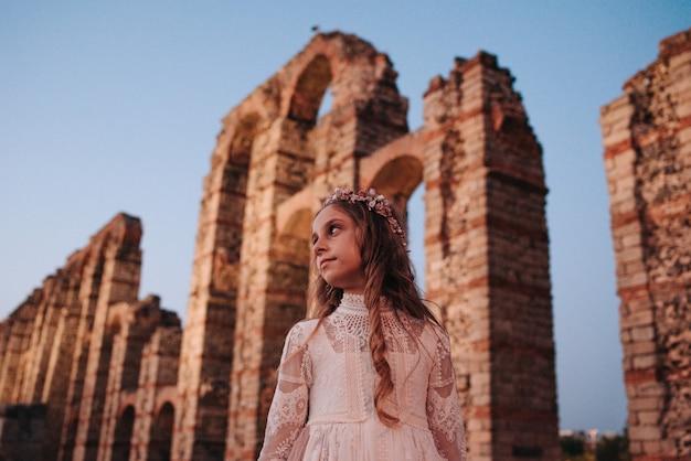 Rapariga loira com cabelo encaracolado com vestido de comunhão em mérida