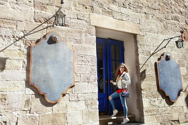 Rapariga loira com calça azul fica diante de uma porta azul