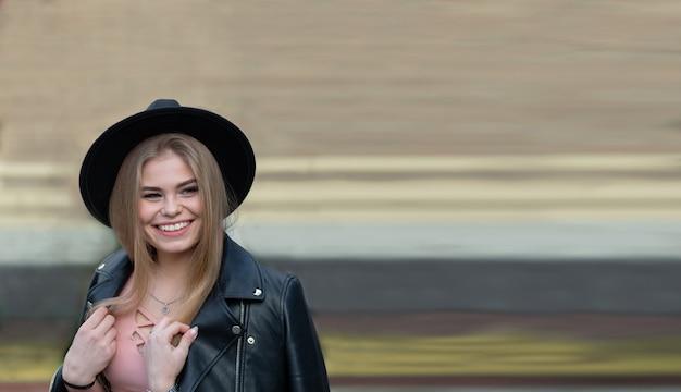 Rapariga loira com chapéu e roda gigante na cidade moderna